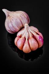 Fresh garlic bulbs on a black background.