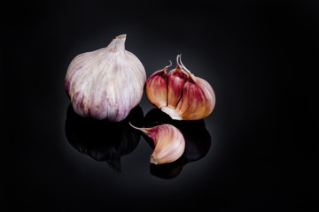 Garlic with reflection on black background.