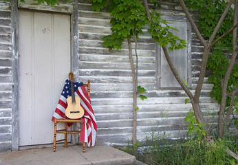 guitar on American flag with wood chair by rustic wooden door
