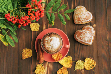 a cup of coffee cappuccino with cinnamon, gingerbread in heart-shaped form, yellow leafy leaves on a wooden table