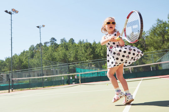 Happy little girl playing tennis