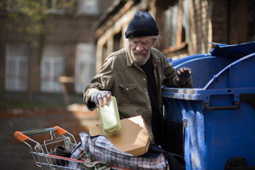 Homeless man searching for empty bottles and other stuff for recycle. Tramp trying to earn money by bringing emty bottles to recycle point.