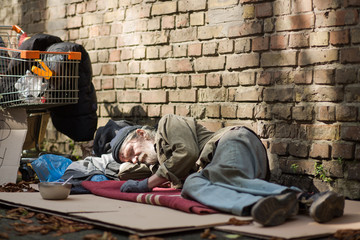 Sleeping homeless man lying on cardboard. Tramp lying by the brick wall, his posessions on the ground and in shopping cart.