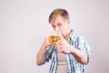 Happy young man drinking beer mug and showing thumbs up