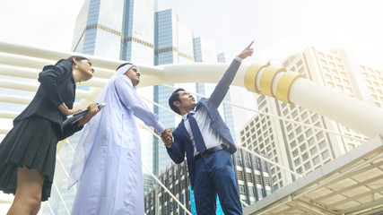 team asian business people smart man and woman talk and shake hand the arab man at outdoor city building