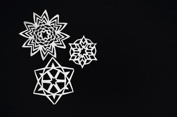 snowflakes cut from paper on black background, Christmas texture or background