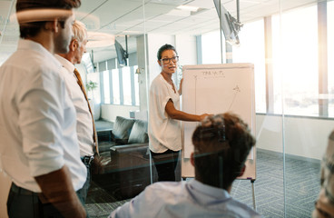 Businesswoman giving presentation to colleagues using flip board