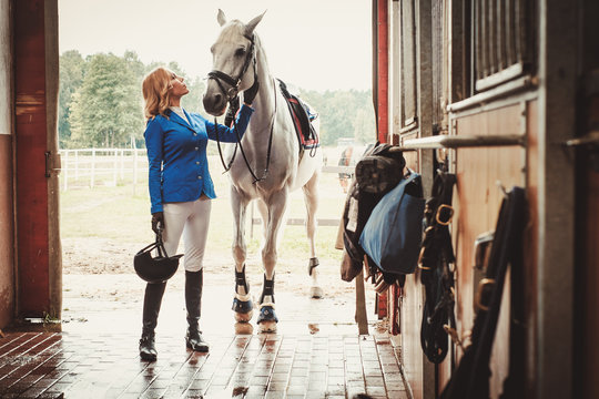 Middle-aged woman with her horse in a stall