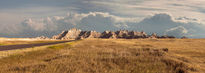 Panorama of badlands national park with vista of mountain range with large clouds in background Wall mural