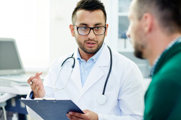 Young doctor consulting one of patients after treatment or examining