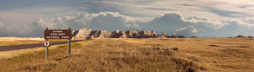 Poster Natural Park Wide landscape panoramic of badlands national park with signage entering into storm clouds