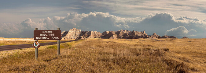 Poster Natuur Park Landscape panorama of badlands Rocky Mountain range, clouds, and grassland with sign
