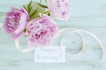 """Greeting card, peonies and the inscription """"Happy Birthday"""" on a turquoise background"""