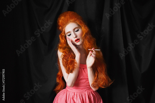 A Smoking Woman With Pale Skin And Long Curly Red Hair In A Pink