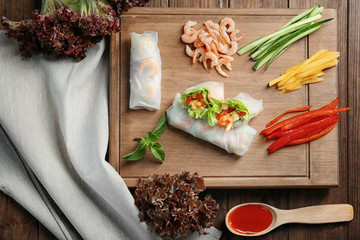 Composition with fresh spring rolls in rice paper and ingredients on table