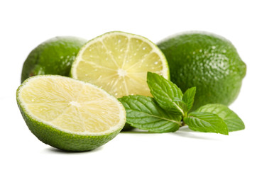 green mint, two limes with half of a juicy lime isolated on white background
