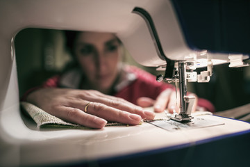 Woman at sewing machine, focus in hands
