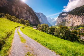 Wall Mural - Majestic view of alpine village. Swiss alps, Lauterbrunnen valley, Staubbach waterfall, Europe.