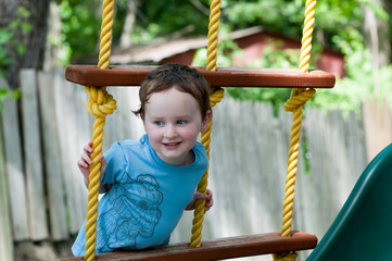 Happy little child boy climbing on the rope ladder outside