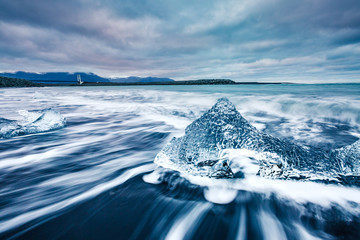 Ice fragments on black sand. Popular tourist attraction. Location Vatnajokull, Jokulsarlon lagoon, Iceland, Europe.