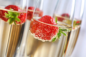 Glasses of delicious wine with strawberry, closeup
