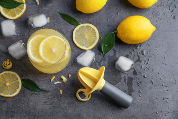 Composition with lemon juice, ice and squeezer on gray background