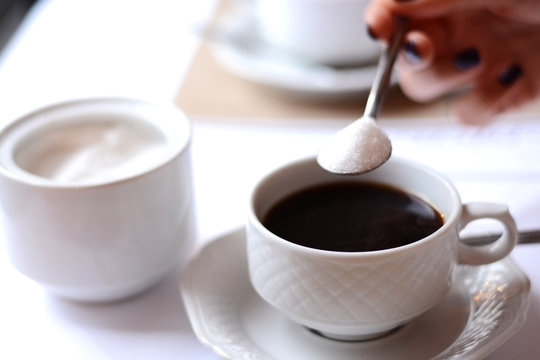 Unhealthy drink with woman hand adding too much sugar on a coffee