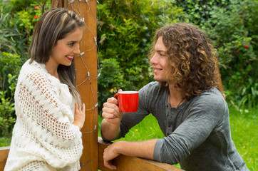Happy couple in love at outdoors and smiling, man holding a red cup of coffe an looking her girlfriend, in a patio backyard
