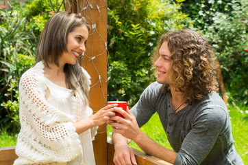 Happy couple in love at outdoors and smiling, man sharing his cup of coffe to her girlfriend an looking her girlfriend, in a patio backyard background