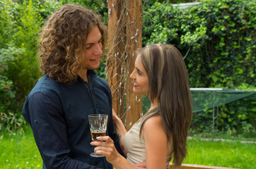 Happy couple in love at outdoors and looking at each other, wearing casual clothes and holding a glass of wine, in a patio backyard background