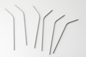 High angle view of six metal drinking straws scattered on white background