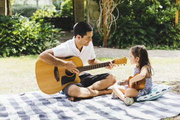 Father having a picnic with daughter and playing guitar