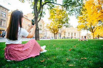 woman sitting on th grass and taking picture of old beuilding