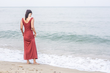 Beautiful girl standing by water edge on the beach wearing red dress
