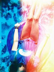 light leak cross processed image of girl in rainbow tee in floatie in blue swimming pool
