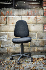 An office chair left by a brick wall