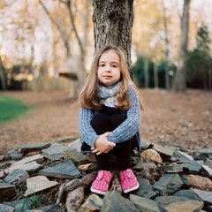 Portrait of a beautiful young girl with a scarf sitting by a tree