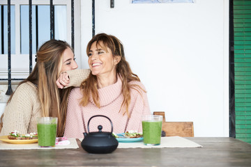 Mother and daughter sitting at wooden table while having lunch