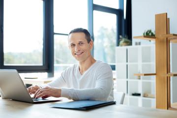 Cheerful positive businessman enjoying his work