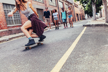 Young girl skateboarding with group of people walking
