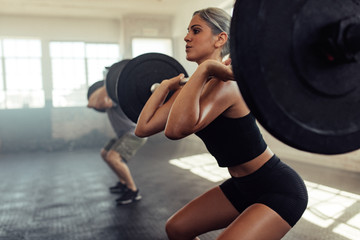 Female working out with barbell at gym