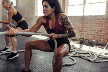 Muscular women pulling ropes at gym