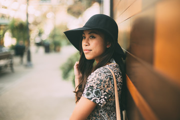 Attractive Young Woman In Sun Hat Leaning Against Wall