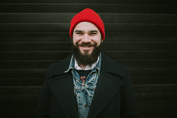 A Man Wearing a Red Beanie and Smiling
