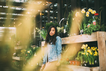 Attractive Young Woman Leaning Against Plant Shelves