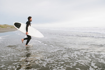 Surfer running into the ocean with surfboard, New Zealand
