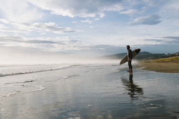 Surfer watching waves from beach, New Zealand.