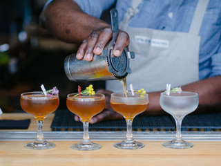 Man wearing apron pouring cocktails at bar