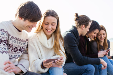 Smiling teenage friends looking their smartphones outside.