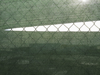 Torn green fabric covering chain-link fence
